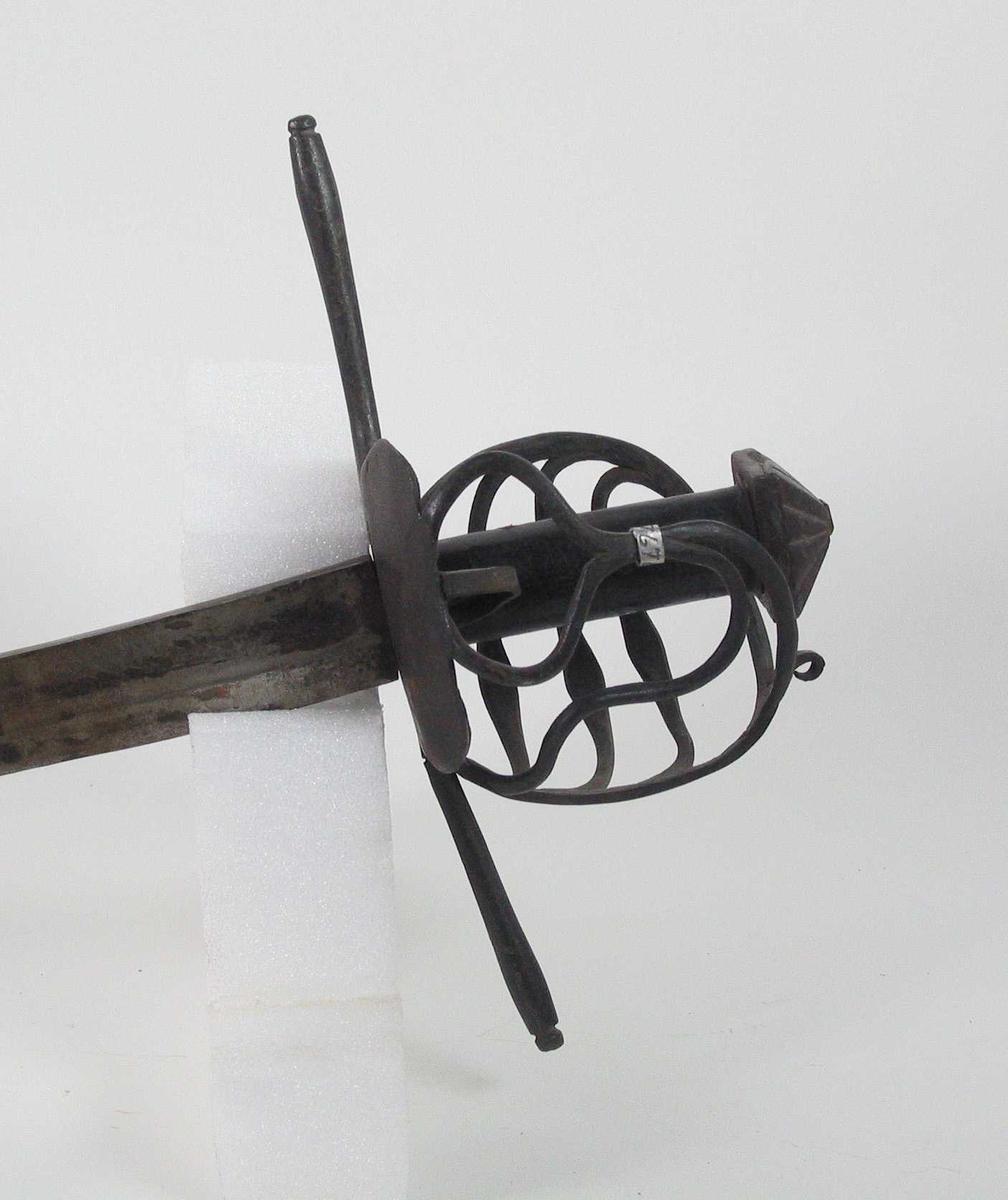Pyramideformet knapp med strekdekor. Asymmetrisk kurvfeste med tre sidebøyler med riflede fortykkelser på midten mellom håndbøylen og kurvens ytterkant. Innsiden har 2 sidebøyler. Kurvens basis består av nyreformet parérplate. Tommelbøyle på innsiden. Rette parérstenger med riflede fortykkelser på endene med dråpeformet avslutning. Tregrep med nyere jerntrådvikling. Enegget krum klinge med gjeddenebb og tre smedstempel på venstre side.