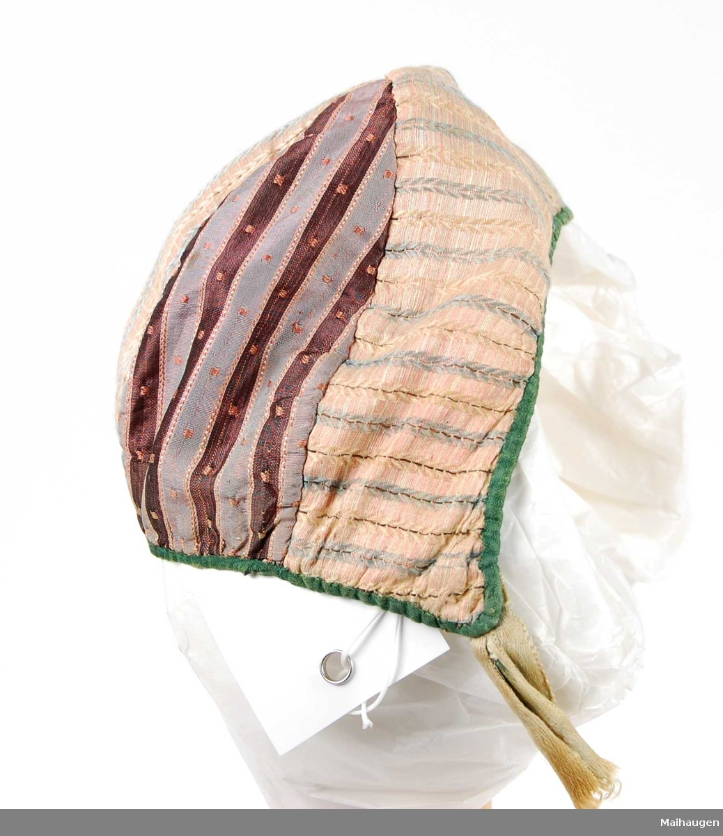 Lue i tre deler:  pannestykke med midtsøm, tre trekantete stykker søm møtes i en spiss på pannestykket. Sydd med spilesøm av stripete rosa, lysblått og gult silketøy. Midtre nakkestykke er av samme tøy. To partier i smalstripet rips i brunt, gråfiolett med rosa prikker. Kantet med grønt silketøy. Fór av grov bomull. Rester av knyttebånd.
