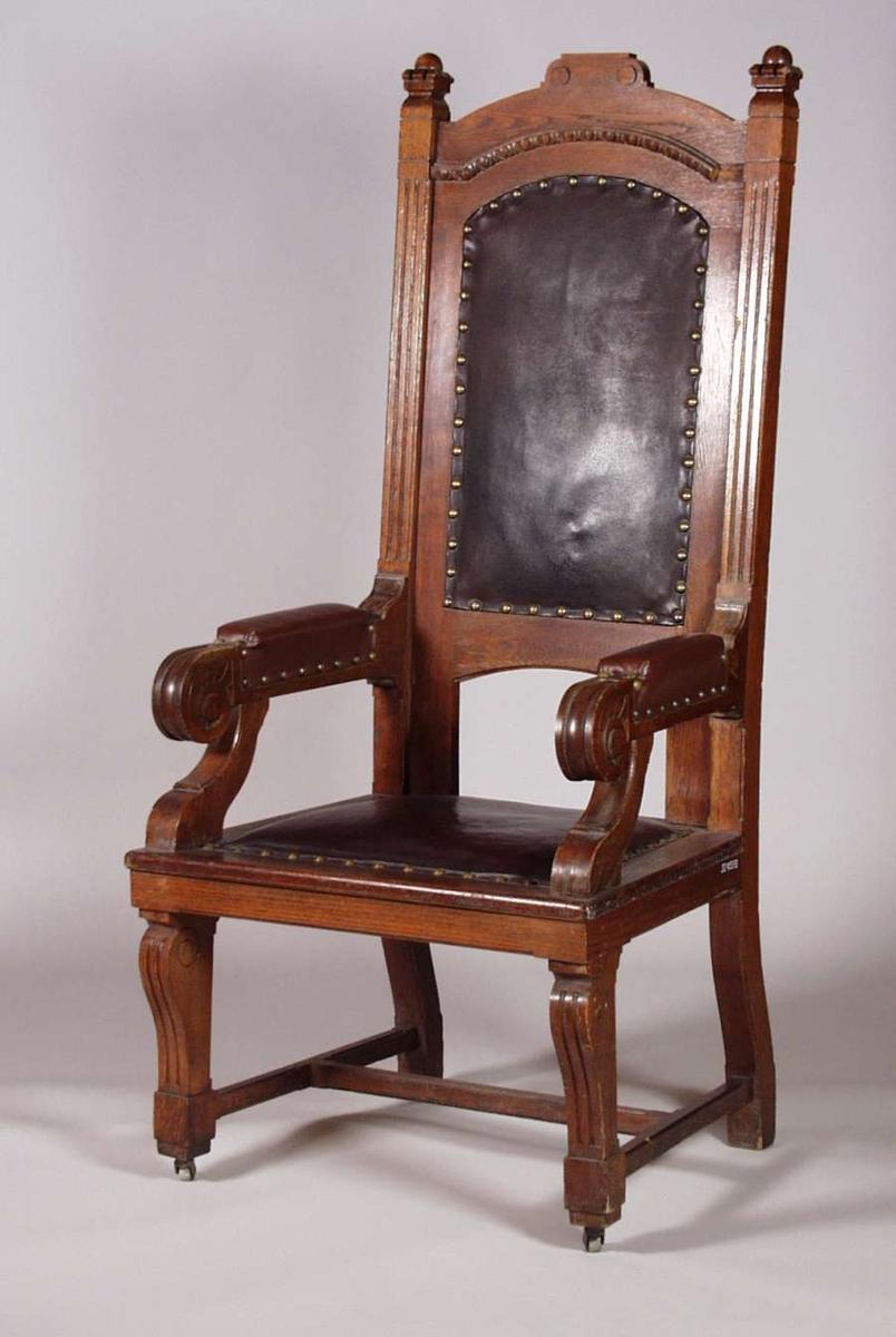 Dommerstol i eik med høy rygg og polstret sete, rygg og armlener i brun skinnimitasjon. Skinnimitasjonen er festet med messingstifter. Stolen har hjul. Utskåret dekor på stolrygg.