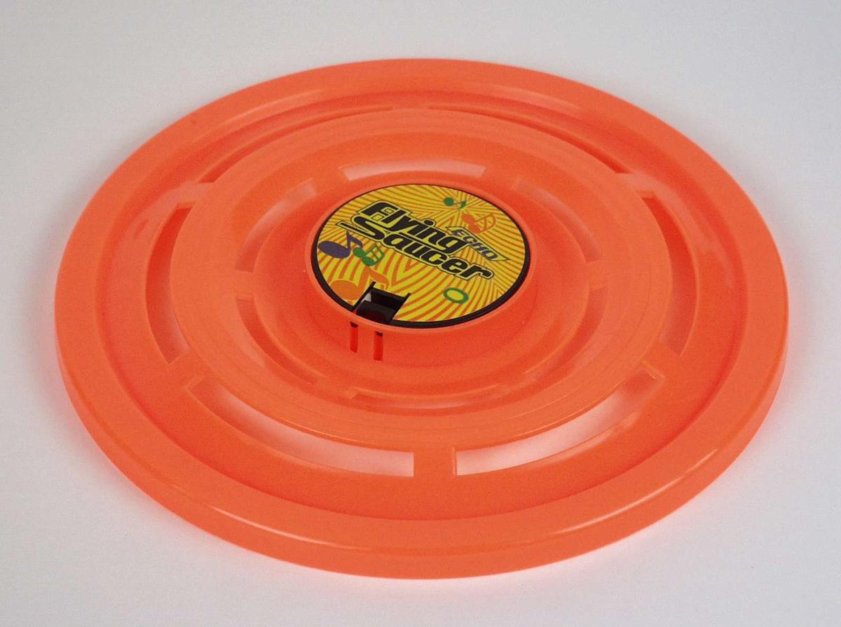 Oransje plastskive som ligner en ufo. Den er batteridrevet og lager pipelyd.
