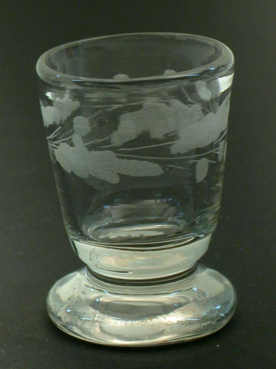 Rundbundet beger med rudimentær stett som nesten direkte forbinder begeret med en tykk fot. Glasset har ekeløvsgravyr.