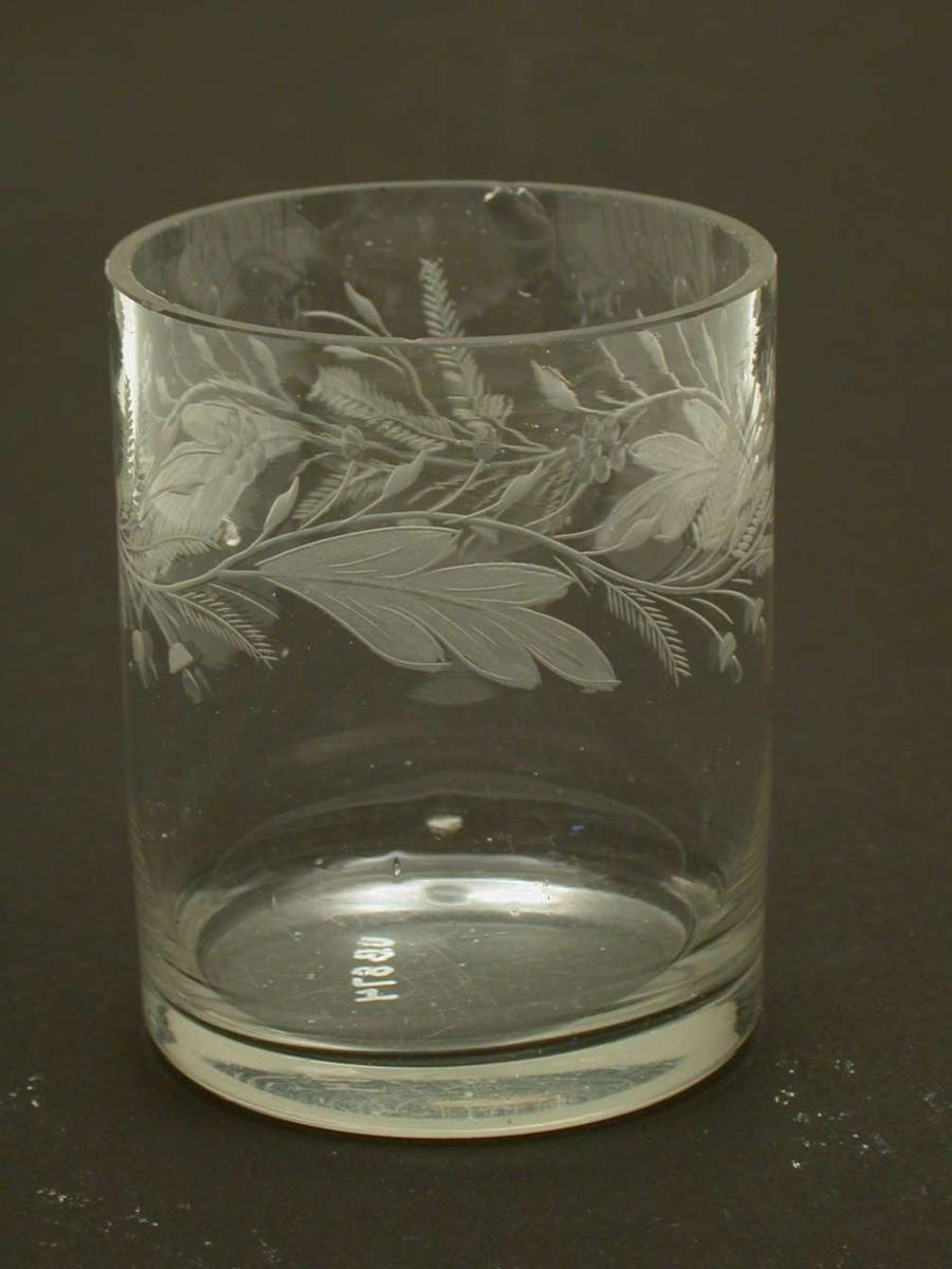 Glass med gravert og olivenslipt blomsterdekor. Det er små hakk i randen på glasset.