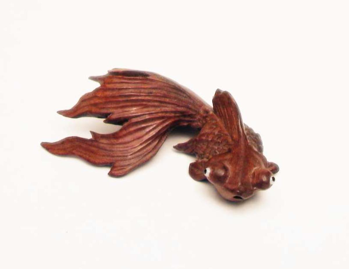 Kinesisk gullfisk utskåret i tre. Den har stor hale og utstående øyne.