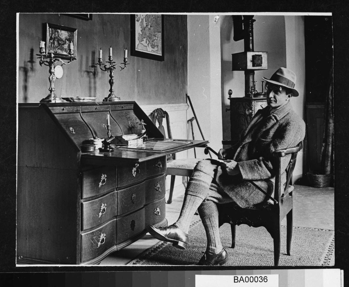 Fotografi av mann sittende i armstol ved skriveskatoll ikledd hatt med bredt silkebånd, halvlang ytterfrakk i grovt materiale, en stokk ligger over fanget; nikkers og lange ullstrømper i korte spaseresko.