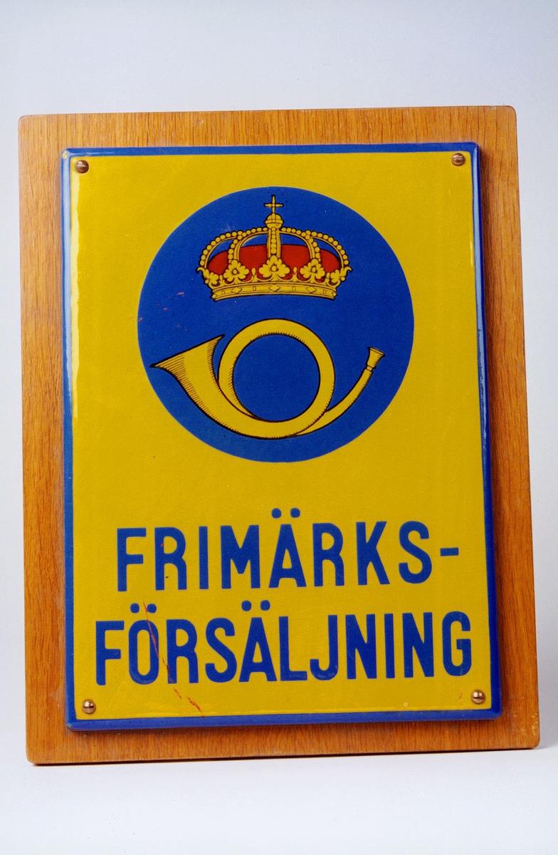 Gult og blått lakkert postskilt.Svensk postskilt. Tekst: Frimarksforsaljning. Posthorn med krone.