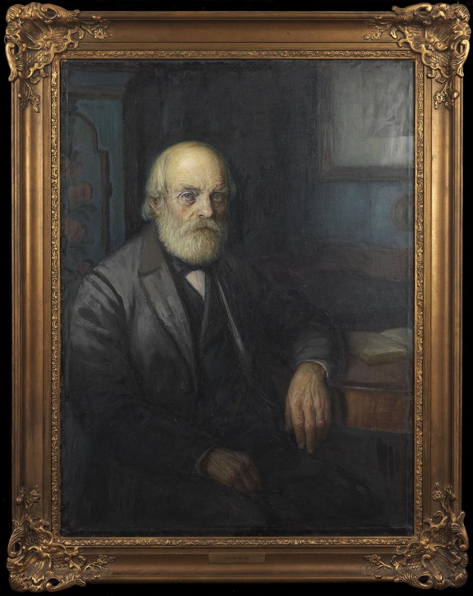 Gammel mann i interiør, sittende, høyrev., knestk., hvitt hår og skjegg, h. arm på bordet, gråsvart dress, mørkgrønn vest