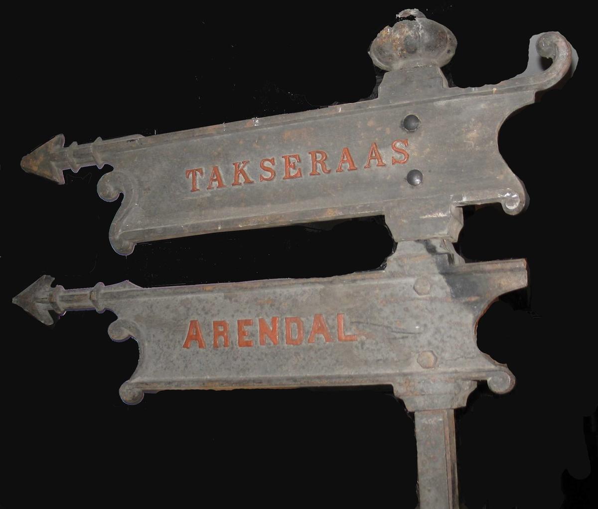 Stolpe m 2 henvisningsskilt med pil mot Arendal og Kolbjøernsvik. Skiltsystemet består av stolper i massivt jern, samt skilt og toppkuler som skrues fast til stolpen, det er skruehull i skilt og kuler. Kulene er ikke helt runde, Selve skiltene er elegant utformet med enkel akantuspynt i begge ender. Det var svak rødfarge på bokstavene på Arendal og Kolbjørnsvik. Dette er forsterket da skiltene ble montert i ustsillingen 2001.