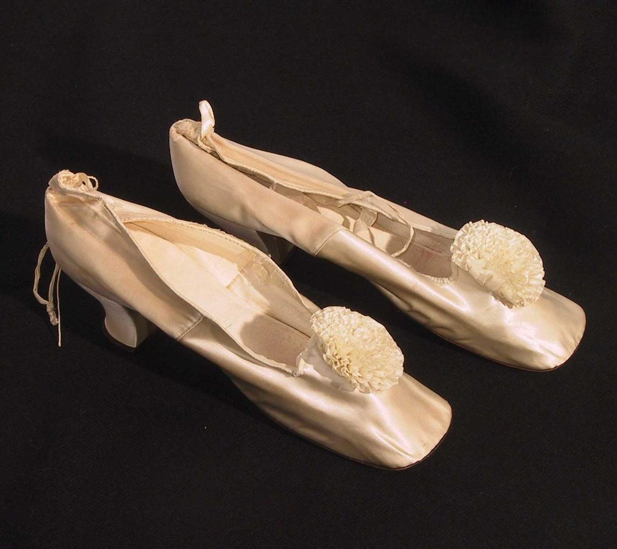 Form: Litt inntrukket hæl, dyp åpning med nesten firkantet avslutning foran. Liten hempe bak. Silkesnor for knyting ved vrista på ene siden på den ene skoen, merke etter bånd også på den andre siden og på den andre skoen. Blomst av silkebånd påsydd foran.