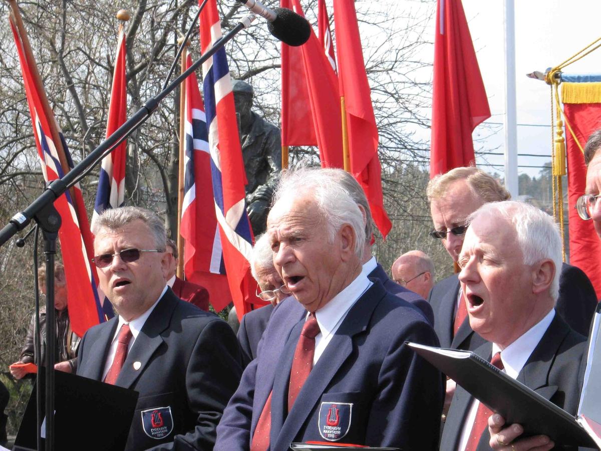 1.mai på Eydehavn. Eydehavn Mannskor synger. Flaggborgen i bakgrunnen. Nærbilde av tre sangere:  T.v.  Svein Hvidsten, i midten Axel Dahlen, og t.h. Arne Kruse.
