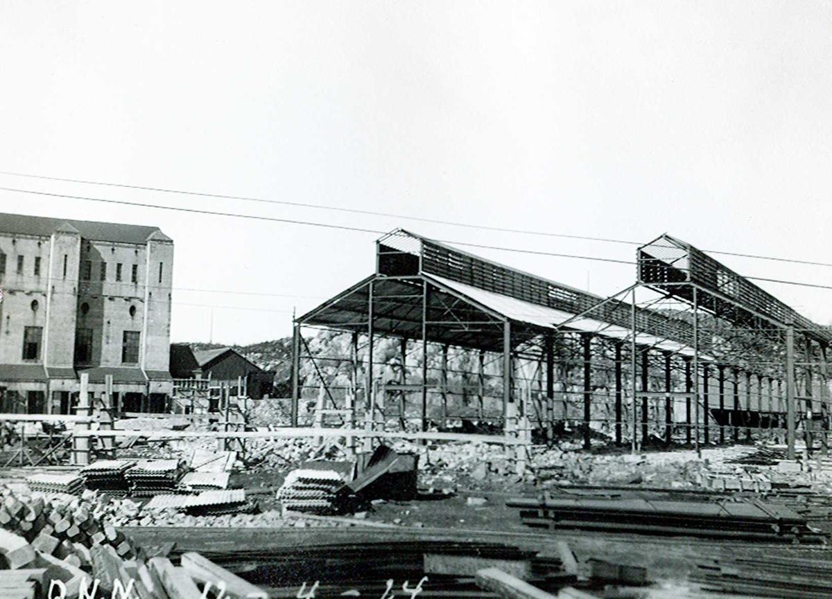 """""""12/04-1924"""" Nitriden. Stekeribygning for steking av elektrodekull under bygging. Til venstre Omformerstasjonen. Bærende konstruksjoner for skinnegang, """"høybane"""", for intern transport med traller trukket av dieseldrevet lokomotiv."""