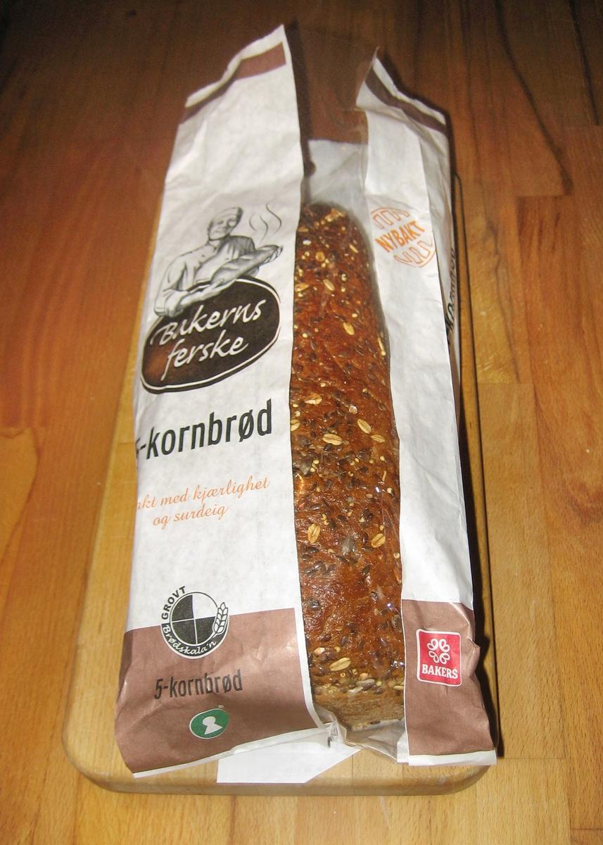 Forsiden: En tegning av en baker i bakerklær holder et nystekt varmt brød. Nøkkelhull ikon på forsiden.