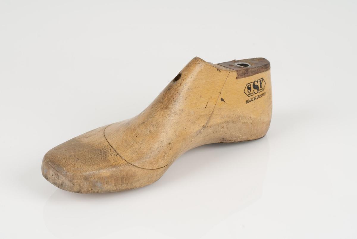 En tremodell i to deler; lest og opplest/overlest (kile). Høyrefot i skostørrelse 38, og 8 cm i vidde. Hælstykket i metall.