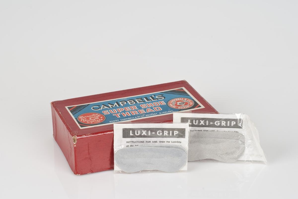 7 pakninger med skipperkapper i en rød pappeske. Hver pakning inneholder 2 skipperkapper av semsket skinn. Påført tekst på pakningen.