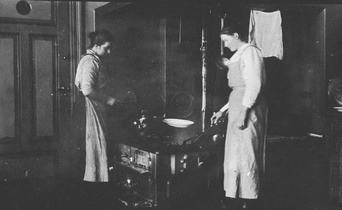 Kjøkken med komfyr og to damer , Hovebyggning på en gård.