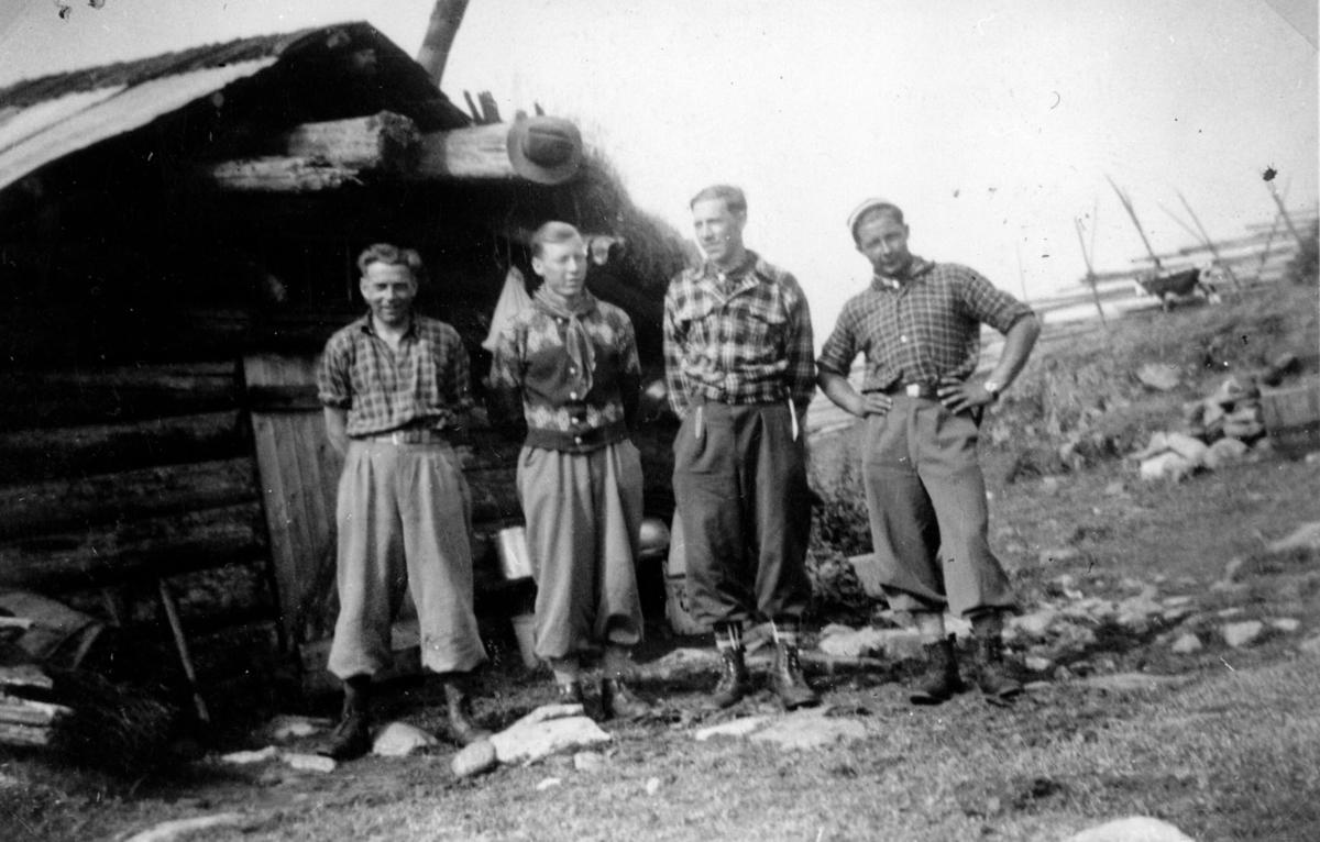 Fire personer foran en tømmerhytte