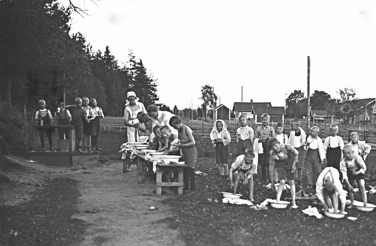 Barn på feriekolonien Sedsvold 1 og 2 på Dal. Guttene vasker seg. Gården Fjeldberg i bakgrunnen er revet.