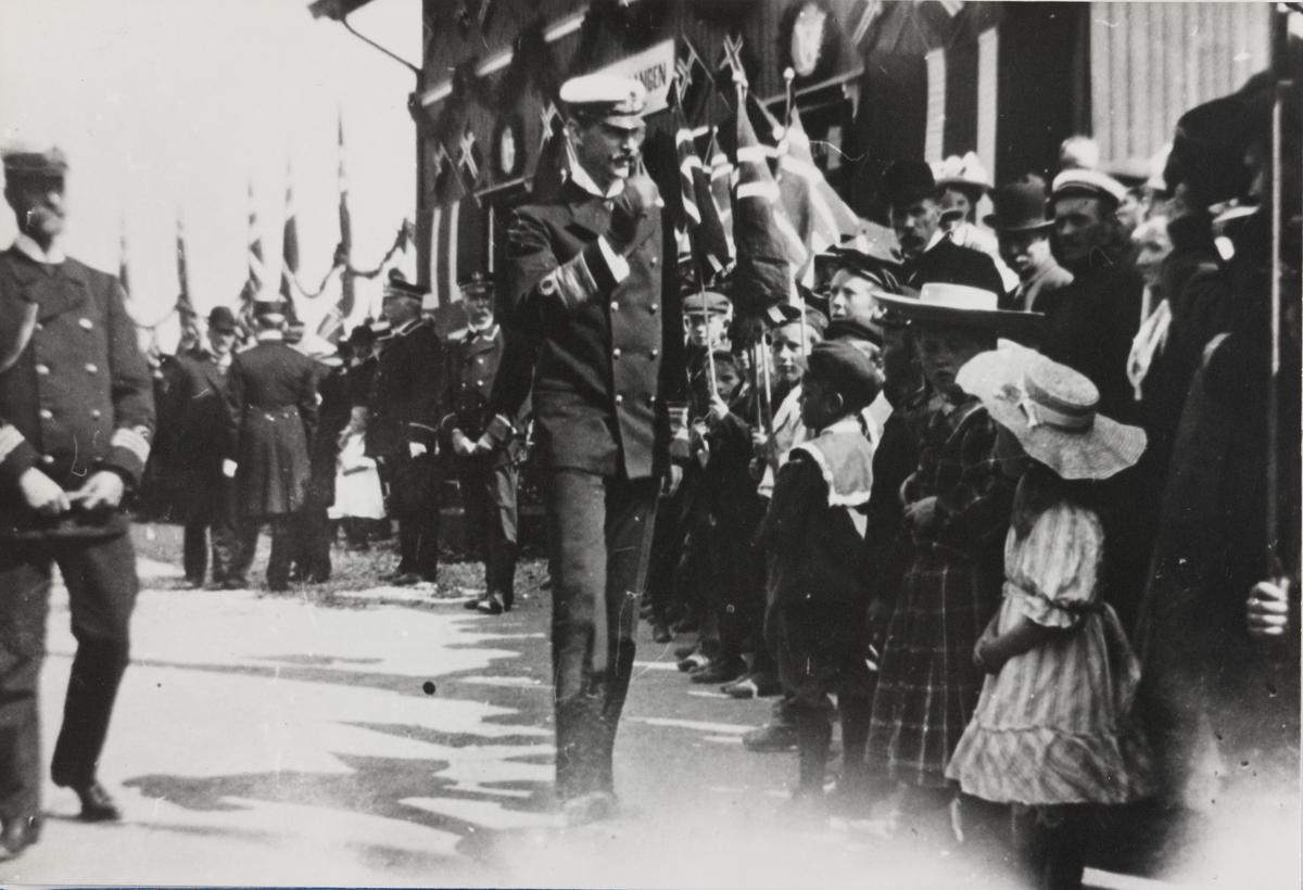 Kong Haakon VII hilser på folk på Bjørkelangen stasjon. T.v. marinekaptein v. Krogh. Foran t.h.: Hjørdis Westbye (UHBs driftsbestyrer Hagen Westbyes datter) og Margrethe Waage i lys kjole (dr. Petter R.Waages datter).