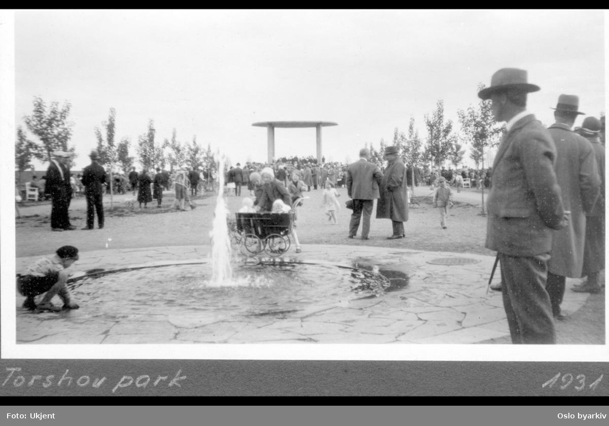 """Publikum ved konsert i musikkpaviljongen i Torshovparken. Barn ved plaskefontenen. Barnevogn. Folkeliv. Albumtittel: """"Torshovparken"""""""