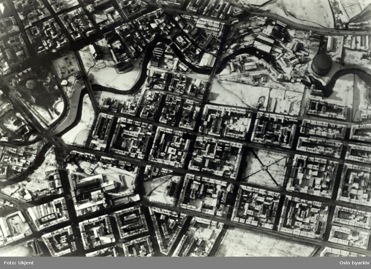 Flyfoto av Grünerløkka. Kvartalsstrukturen med Schous plass, Olav Ryes plass, Grünerhagen. Akerselva. Gassverket på Ankertorget til venstre og gassbeholderen på Kuba øverst til høyre i billedflaten.