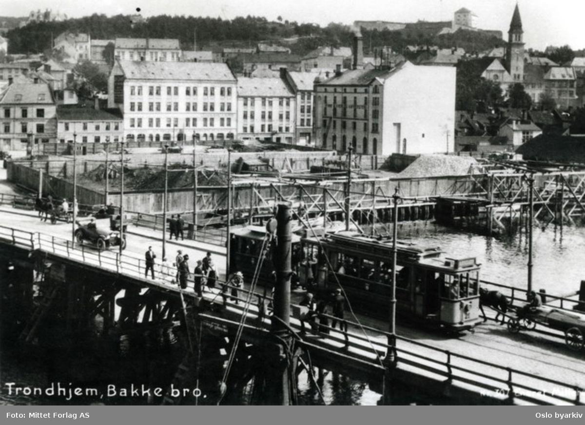 Bakkebro i Trondheim med folkeliv, biler og trikk. Samt en hest og kjerre.