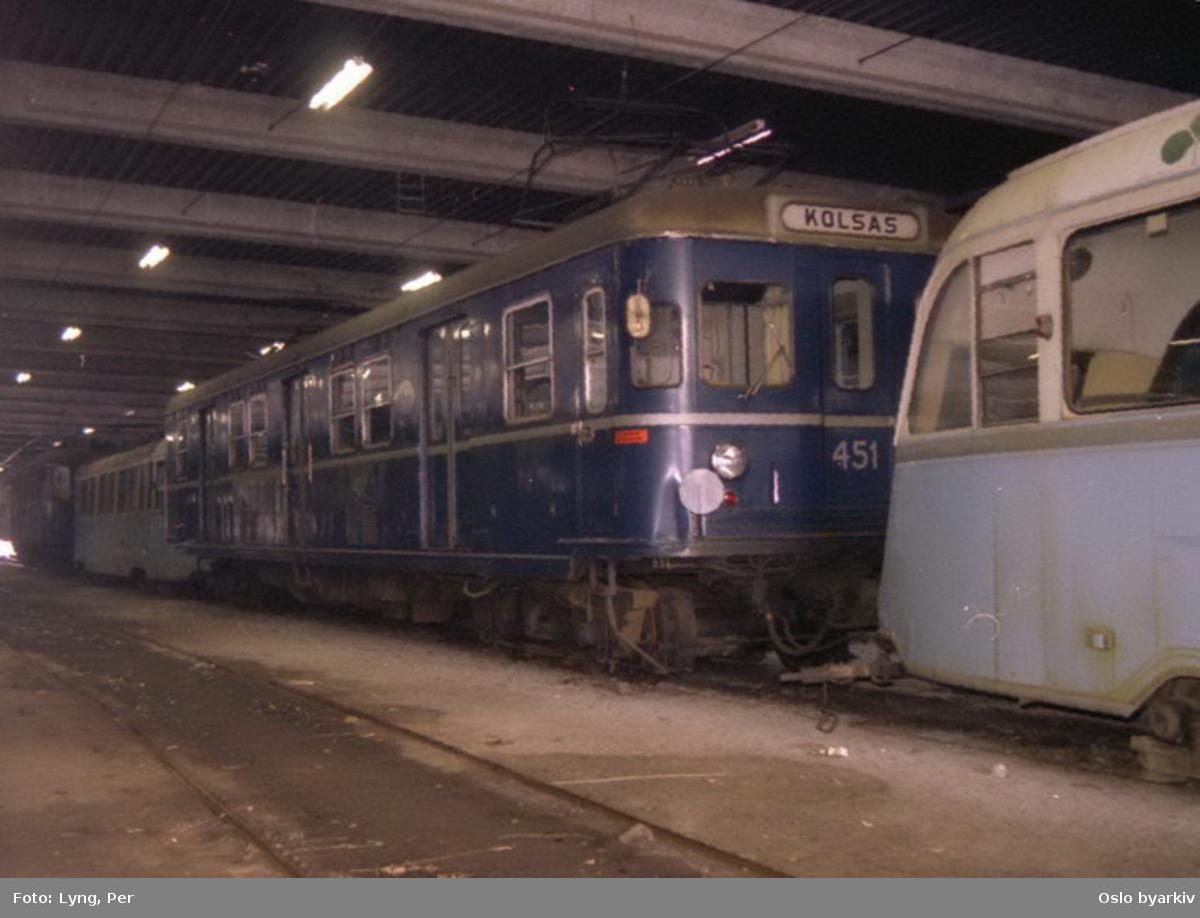 """Oslo Sporveier. Vogn 451 på Kolsåsbanen i """"fryseboksen"""" på Avløs vognhall og verksted mellom to gullfisktrikker. (Vogn 451 var tidligere vogn 1, serie T, inntil 1970, brukt fra 1960 til prøvekjøring som prototyp T-banevogn på Kolsås- og Lambertseterbanen, men overført til Kolsåsbanen som vanlig trafikkvogn. Opphugget 1994.)"""