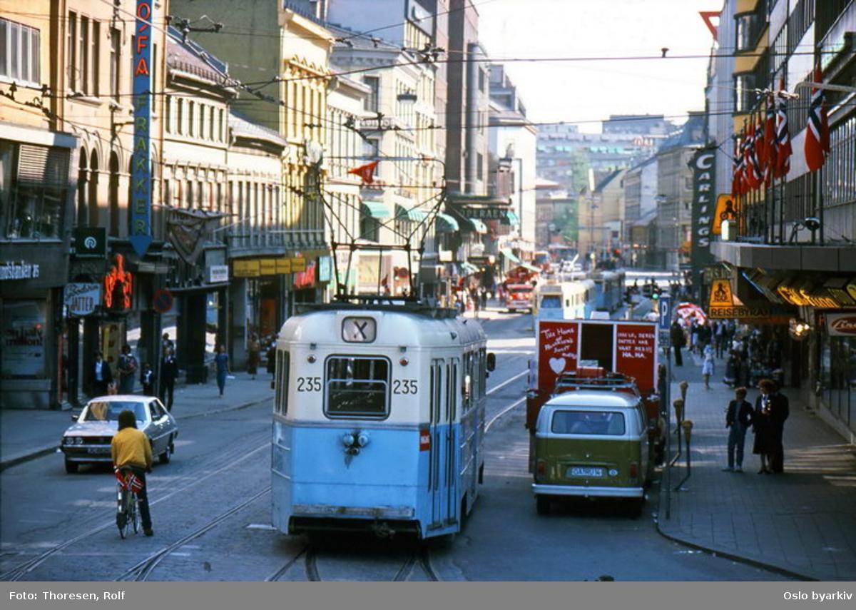 Oslo Sporveier. Trikk motorvogn 235 type Høka MBO, X-vogn, trolig en 17. mai, mange flagg og pent kledde mennesker i Storgata. Gatebilde, trafikkmiljø, butikker, butikkskilt.