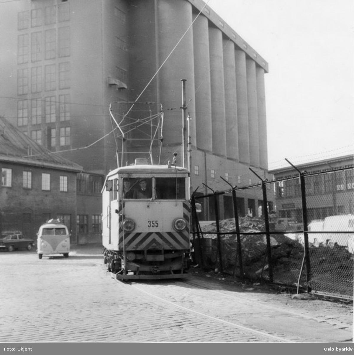 """Oslo Sporveier. Trikk spesialbygd godsmotorvogn type K nr. 355, """"korntrikken"""" på vei mellom den nye siloen og vendesløyfa. Sporet inn til den gamle siloen tok av under vogna og buet av mot venstre (kontaktledningen). Oslo Sporveiers """"radiobil"""" av type VW i bakgrunnen."""