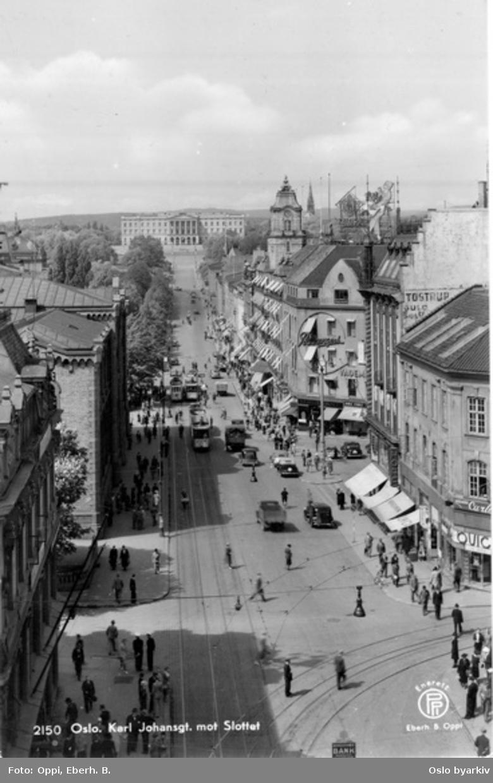 Karl Johans gate fra Egertorget og Akersgata til Slottsbakken. Stortings plass, Brambanigården, Grand Hotel. Trikker, biler, spaserende. Postkort 2150.