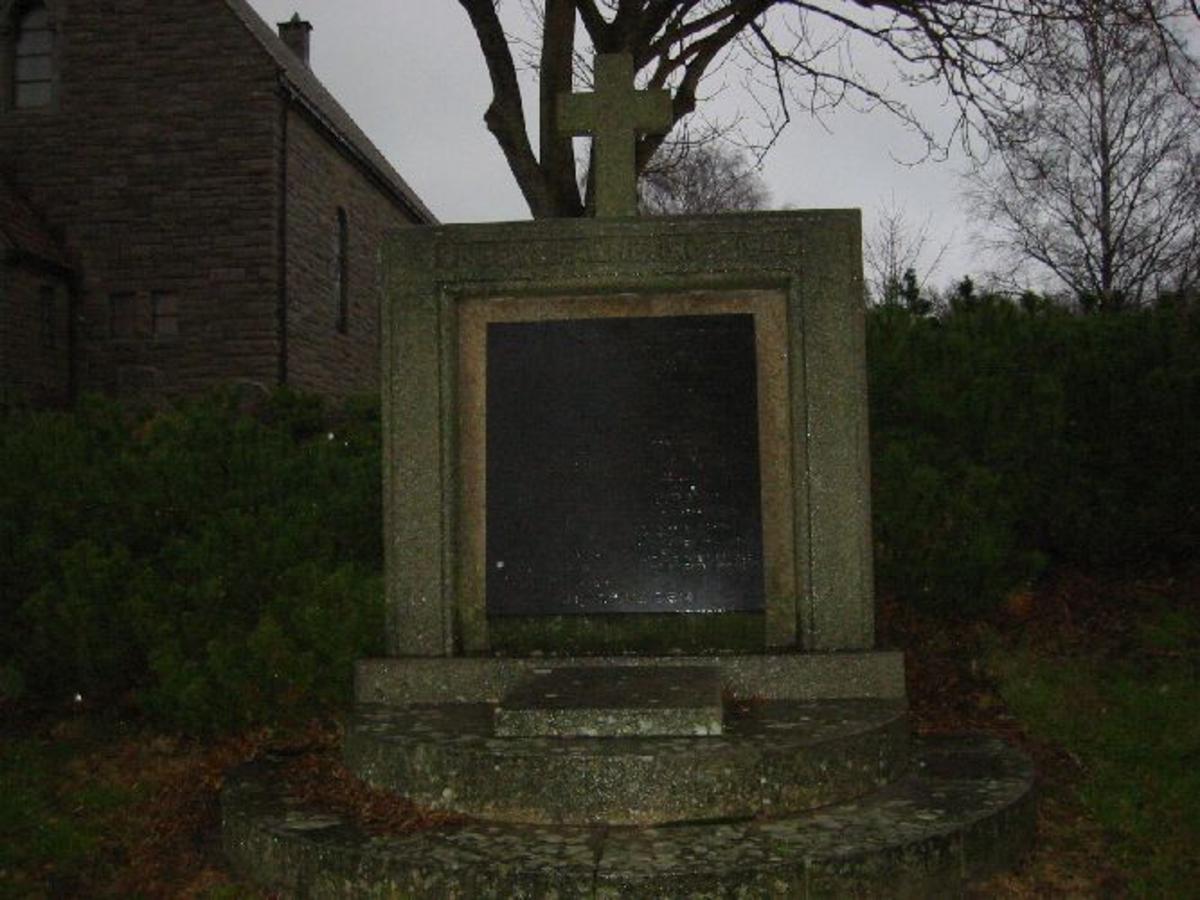 Firkantet bauta med kors på toppen laget i granitt. Polert steinplate i front med inngraveringer.