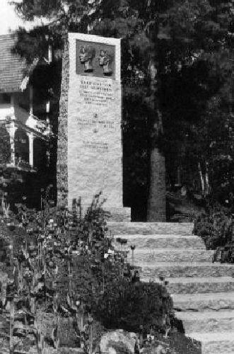 Krigsminnesmerke.Bauta med relieff + tavle i sandtaket. Rå Grorud-granitt med bronserelieff. Høyde 300 cm, bredde 100 cm, dybde 30 cm.