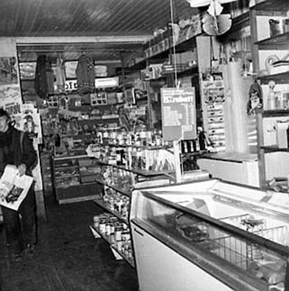 INTERIØR: SKJELVENGA HANDEL, BUTIKK, LANDHANDLERI, EKSPEDITØR, DISK, VARER. Rolf A. OLsen ekspederer kunde. Vekt, kaffemaskin, mineralvann, reklame.