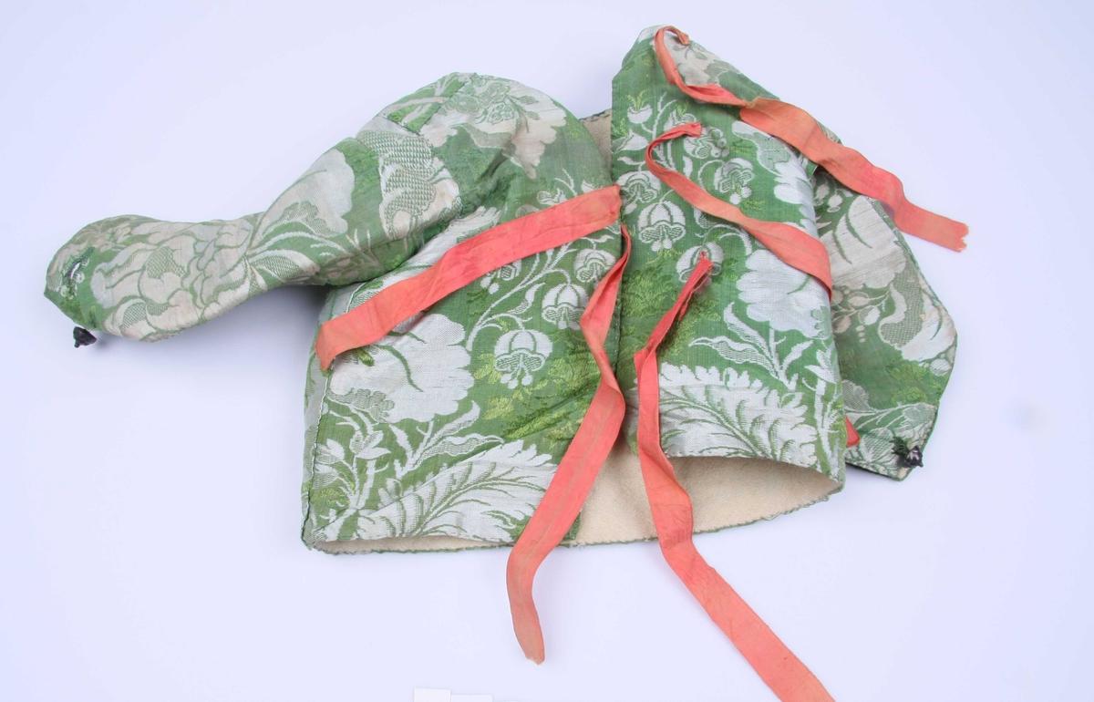 Av brokade i grønt og sølv, storblomstret og med grønne brocherte blomster. Med røde silkebånd til å knyte bak. Sømmene er stukket på retten. Ermene har splitt nederst på yttersiden med tinnknapp og knapphull. Fôr av hvitt ullstoff.
