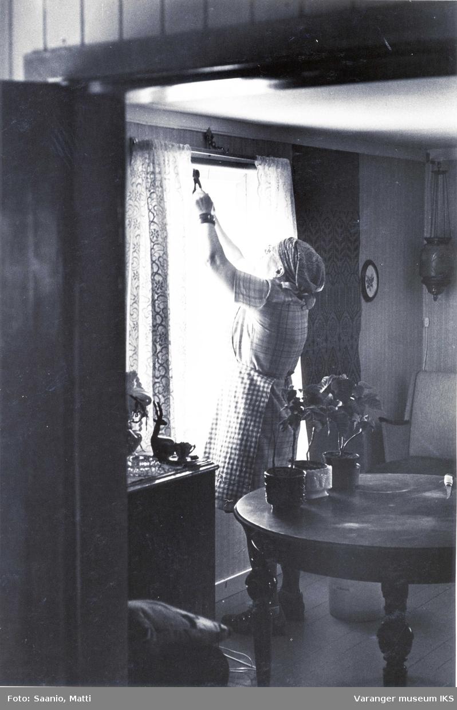 Ida Tuomainen vanner blomster i stua på Tuomainengården 1977