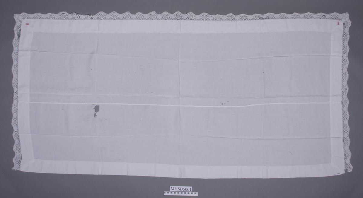 """Linduk med ordinær bomullsblonde. Duken er sydd sammen av to hovedfelt og en kant rundt hele.  Har en vaskerilapp: """"DJ466"""""""