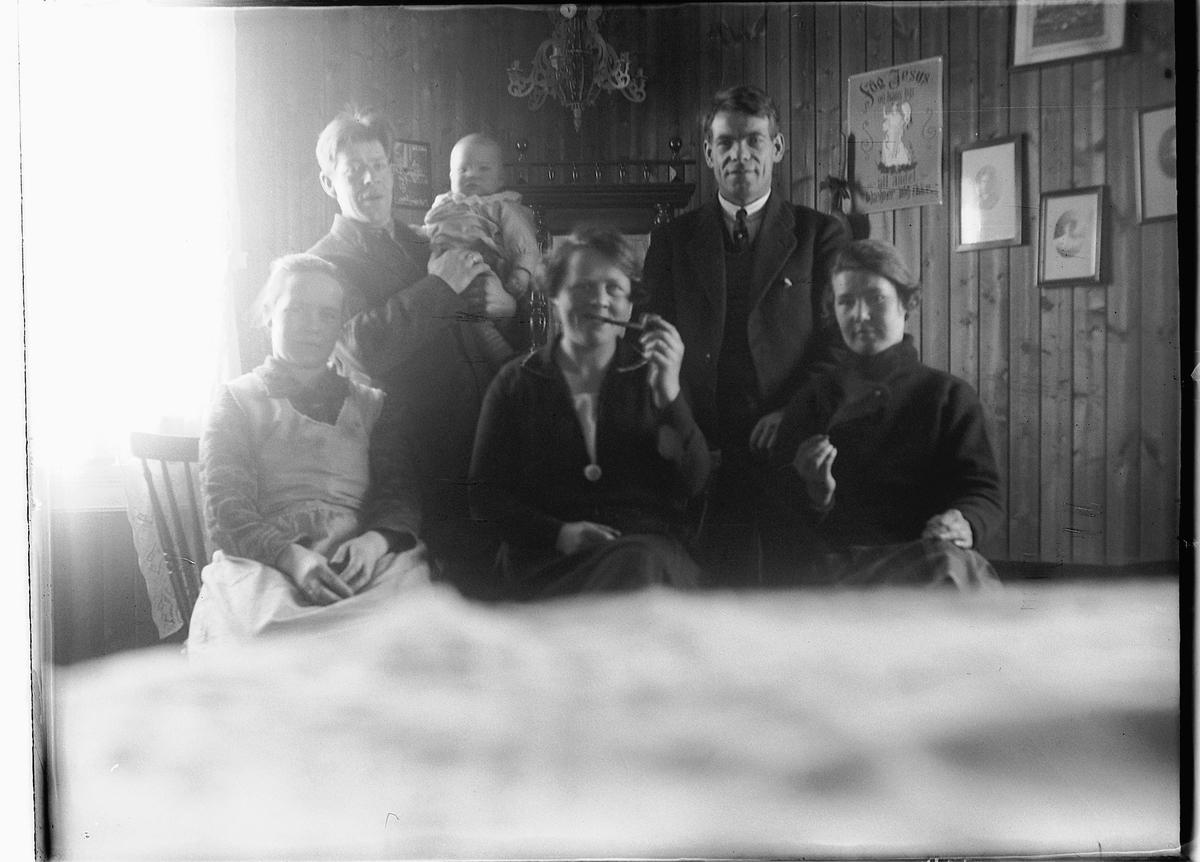 Gr. 6. Familiebilde tatt med sjølutløser. Tre kvinner sitter, to menn bak, barn på armen. Kvinnen røyker pipe.