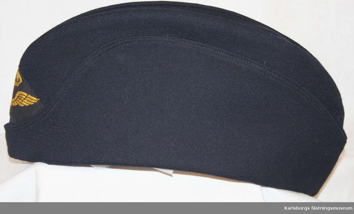 Storlek: 58 Flygmössa m/1930 blå, tillverkad av mörkblå ripsdiagonal försedd med flygemblem manskap fram. Den är försedd med helt slag. Mössan ingår i daglig dräkt flygvapnets personal.