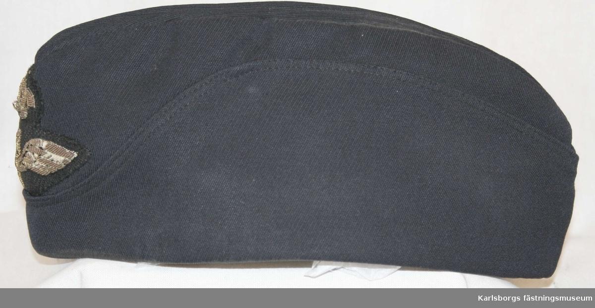 Storlek: 56 Flygmössa m/1930 blå tillverkad av mörkblå ripsdiagonal försedd med flygemblem fram, helt skag. Mössan ingår i daglig dräkt för flygvapnets perrsonal.