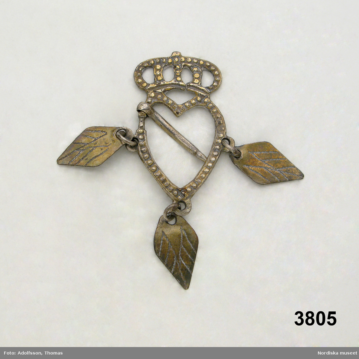 Hjärtformad sölja krönt med sluten krona och med pärlstavsdekor, svagt förgylld. 3 st rombiska hängen, torn för fastsättning i överdelens kragkanter eller på halsklädet. Spricka i kronans bas. /Berit Eldvik juni 2005