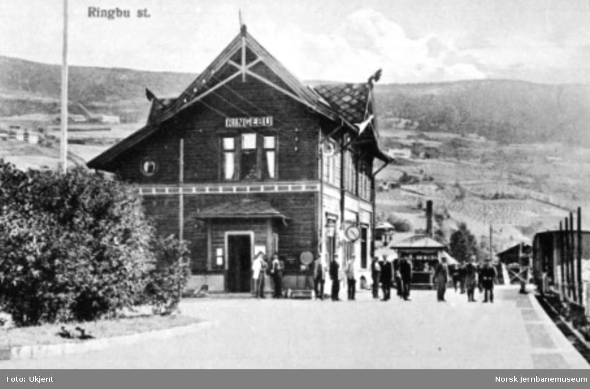 Ringebu stasjon med et godstog i spor 1 og reisende på plattformen