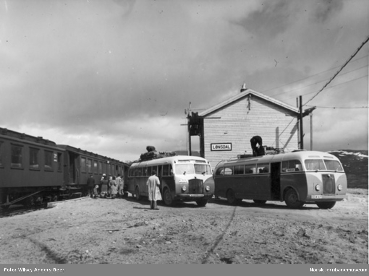 Lønsdal stasjon med reisende som stiger av toget og ventende busser
