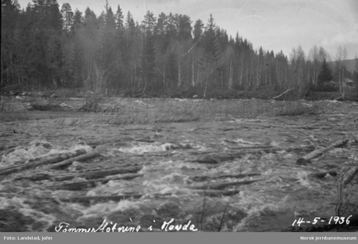 Tømmerfløting i Hovda elv. Tømmeret passerer forbi til høyre mot jernbanebrua.