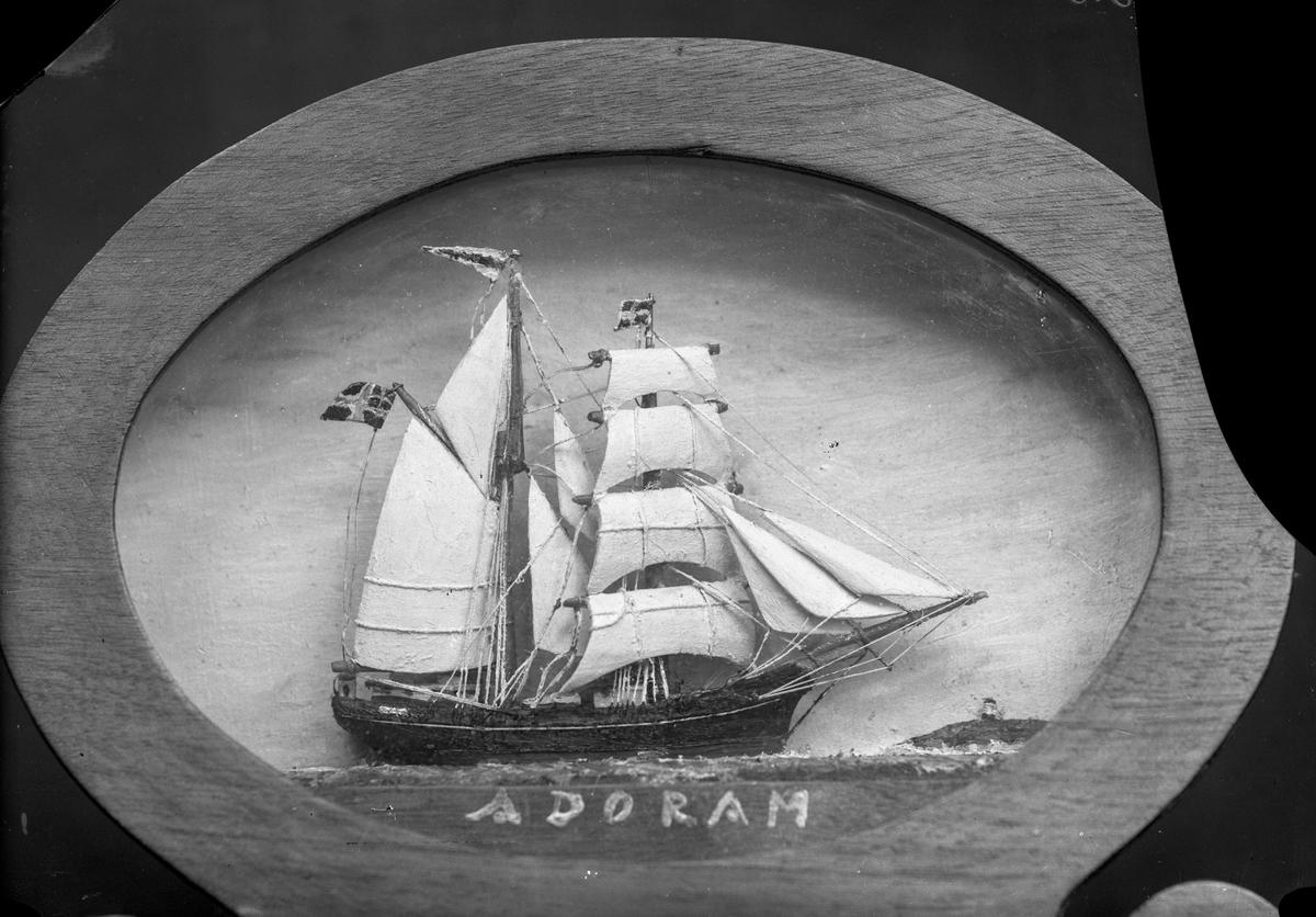 """Avfotografert maleri av skonnerten """"Adoram"""".  Land med fyrtårn i bakgrunnen."""