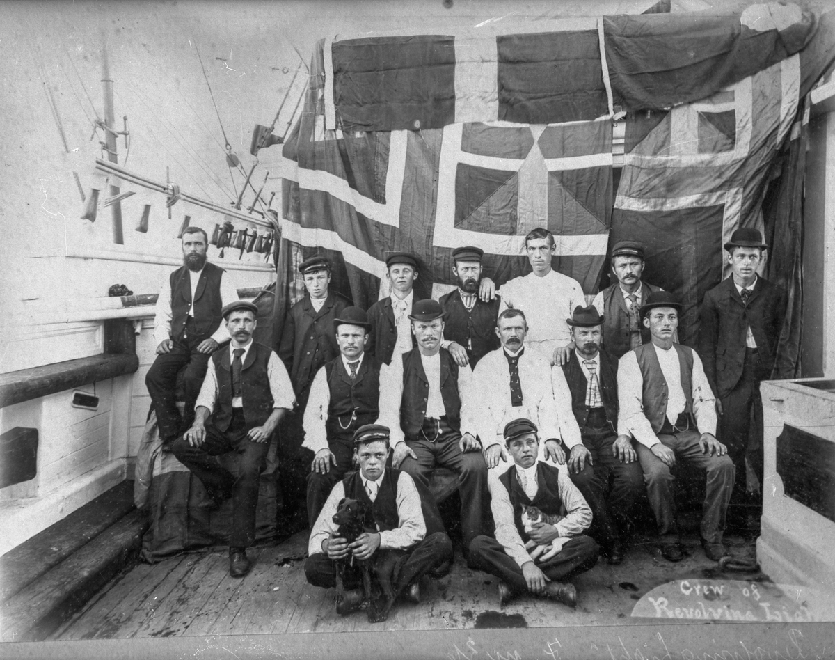 """Mannskapet ombord på skipet """"Revolvig Light"""". De to fremste av mannskapet sitter foran  og holder hvert sitt dyr: den til venstre en liten hund, den til høyre en katt."""
