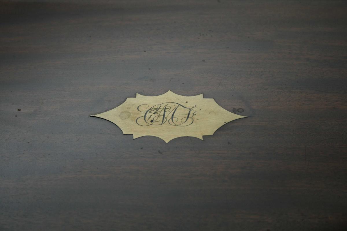 Regtangulært skrin. Når lokket slås opp blir det ei skrå skriveplate. Under skriveplata er det flere rom til oppbevaring av papir og skriveredskaper. I bunnen av skrinet er det en skjult skuff. Messingbeslag, og messingskilt med bokstavene CMF på  på lokket.
