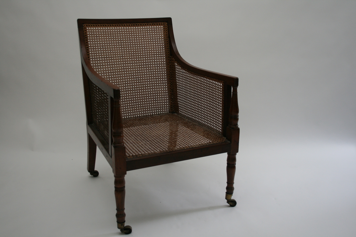 Armstol i mahogni med rørfletting i sete, rygg og sider. Dreide frambein med messingstrinser, små messinghjul bak. Løs sittepute.