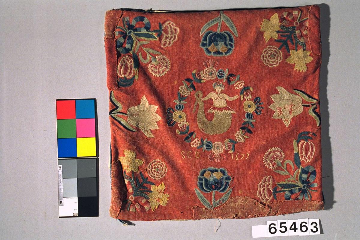 Rød putetrekk  av ull med brodert dekor, bakside i hvitt skinn og mellomstoff av grovt linne.