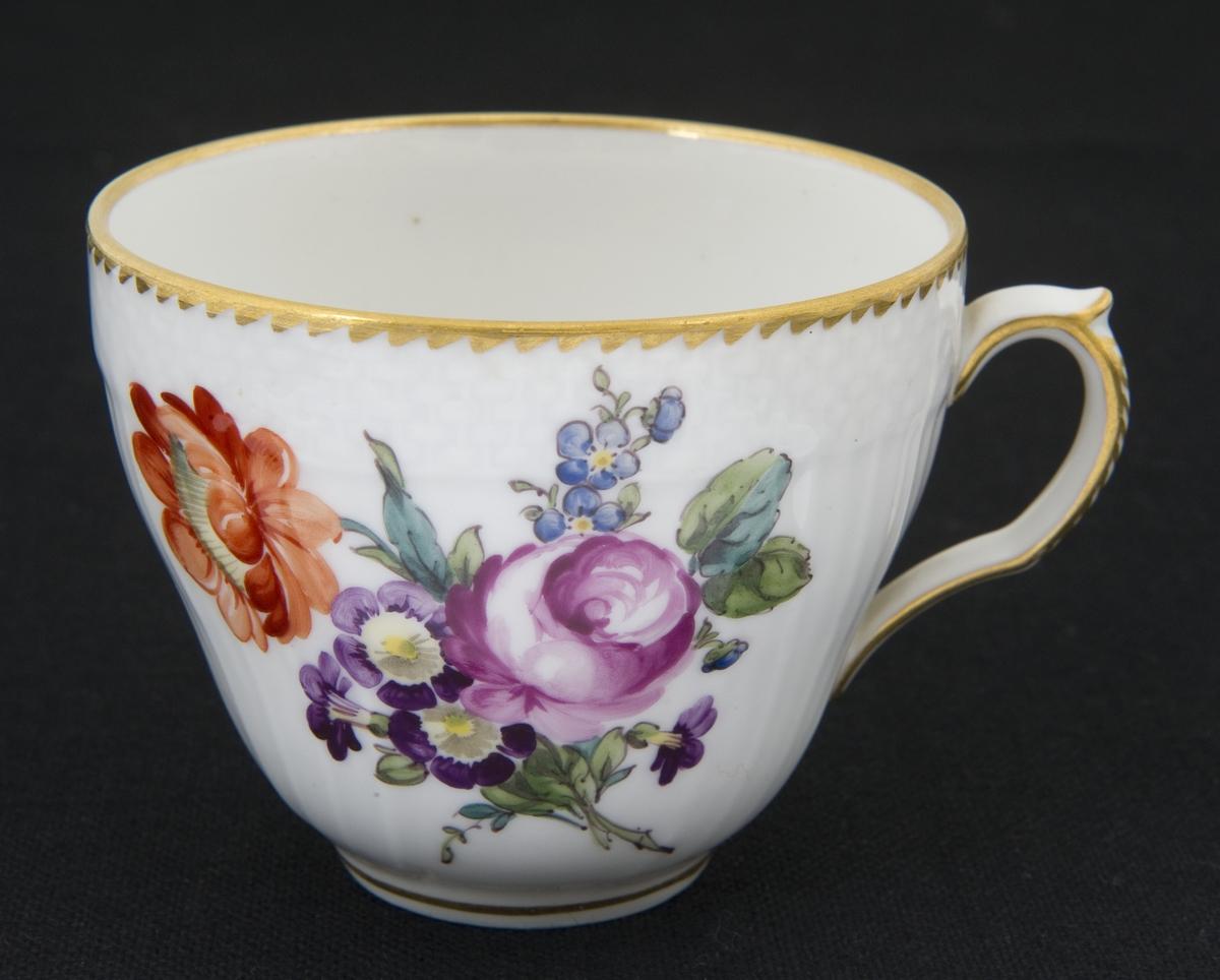 Kaffekopp i porselen med håndmalt blomsterdekor, gullkant og riflet gods. En blomst i bunn av koppen.