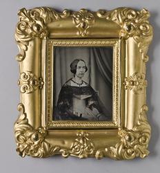 Porträtt av sittande dam i trekvartsprofil.
