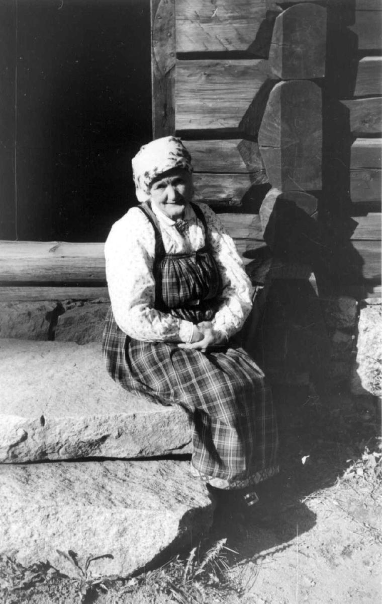 Vert i drakt, oppsynsdame Lina Hansen, i Hallingdalstunet på Norsk Folkemuseum.