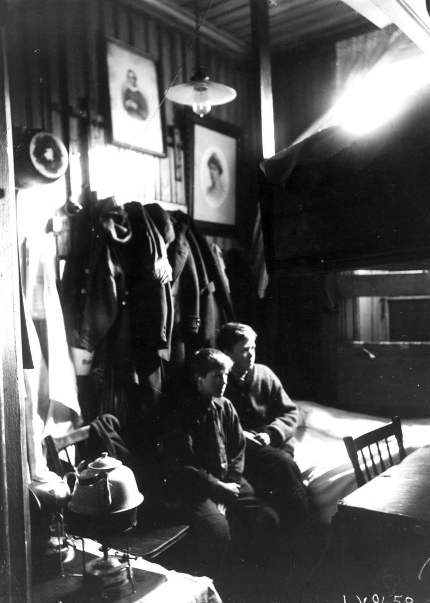 Interiør, Grønlandsstrøket, Oslo. Bebodd bakrom i butikk, 2 gutter sitter mellom seng og kjøkkenkrok med kokeapparat i tett møblert rom. Fra boliginspektør Nanna Brochs boligundersøkelser i Oslo 1920-årene. Se Relaterte objekter.